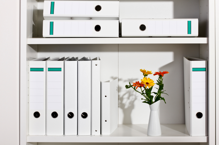 Shelf with white folders and flower vase